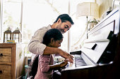 Father teaching daughter to play piano at home. Man is assisting child in playing keyboard instrument. They are at home.
