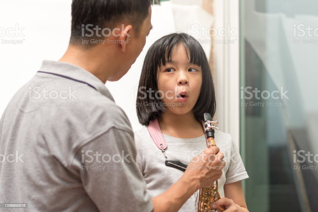 Father teaching daughter to play saxophone. Dad train Asian kid girl...