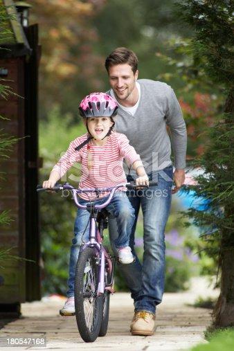 istock Father Teaching Daughter To Ride Bike In Garden 180547168
