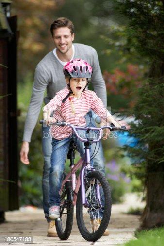 istock Father Teaching Daughter To Ride Bike In Garden 180547183