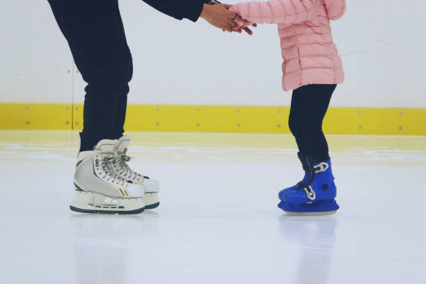 father teaching daughter to skate at ice-skating rink father teaching daughter to skate at ice-skating rink ice skating stock pictures, royalty-free photos & images