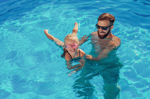 High angle view of beautiful little girl and her father having fun in the swimming pool on a hot sunny summer day, father teaching daughter to swim