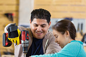 Mid adult Hispanic man is using a cordless drill or screw gun while building something in garage or workshop with elementary age daughter. Father is teaching little girl to use power tools while they spend quality time together.