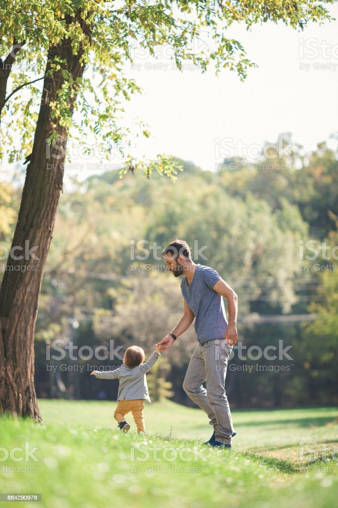 Father teaching his baby boy to walk royalty-free stock photo