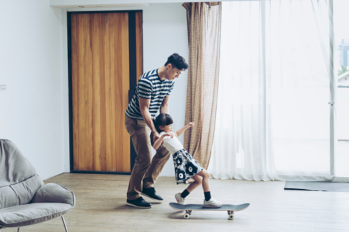 Father teaching his daughter how to skateboard