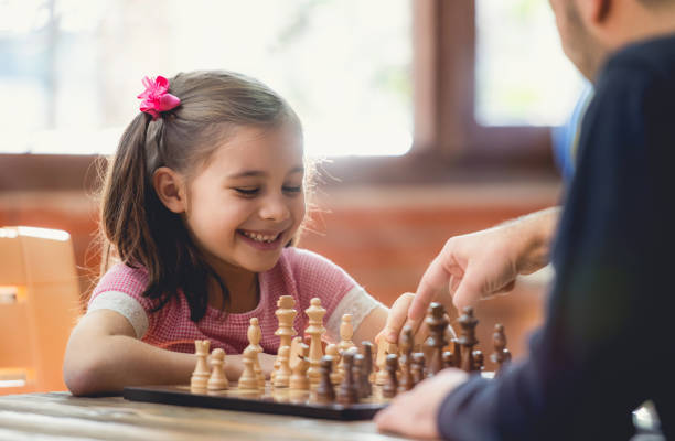 Father Teaching His Daughter to Play Chess At Home stock photo