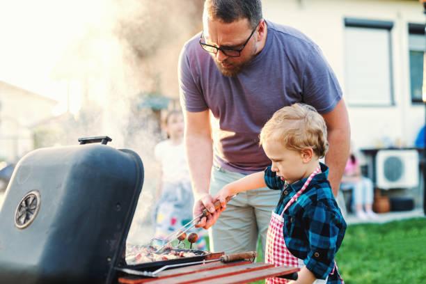 ojciec uczy swojego małego syna, jak grillować stojąc na podwórku w lecie. koncepcja spotkań rodzinnych. - grillowany zdjęcia i obrazy z banku zdjęć