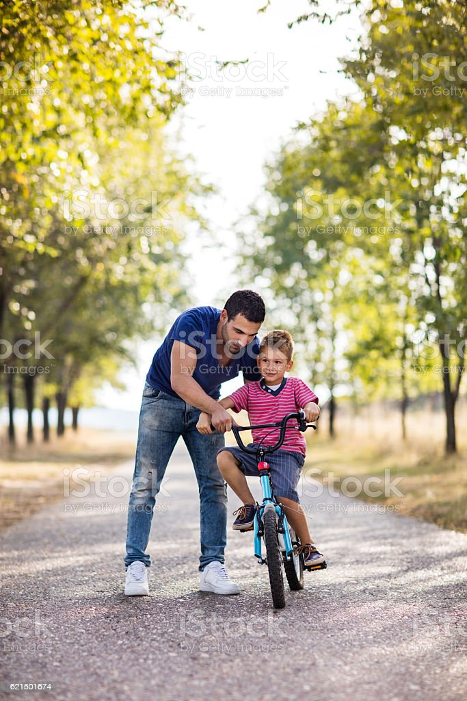 Father teaching his small son to ride bicycle in nature. photo libre de droits
