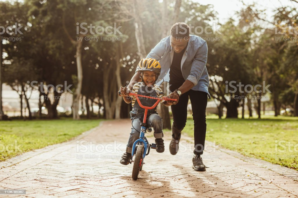 Father teaching his son cycling at park Boy learning to ride a bicycle with his father in park. Father teaching his son cycling at park. Adult Stock Photo