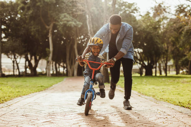 Father teaching his son cycling at park Boy learning to ride a bicycle with his father in park. Father teaching his son cycling at park. showing stock pictures, royalty-free photos & images