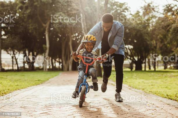 Photo of Father teaching his son cycling at park