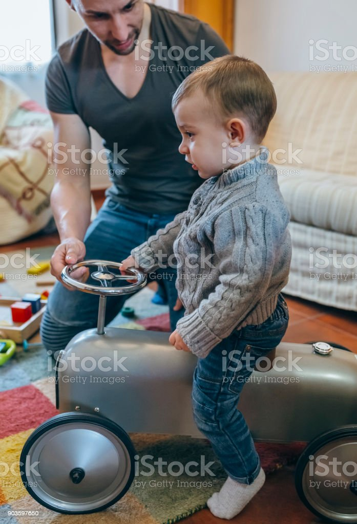 Father teaching his son how to drive small racing car stock photo