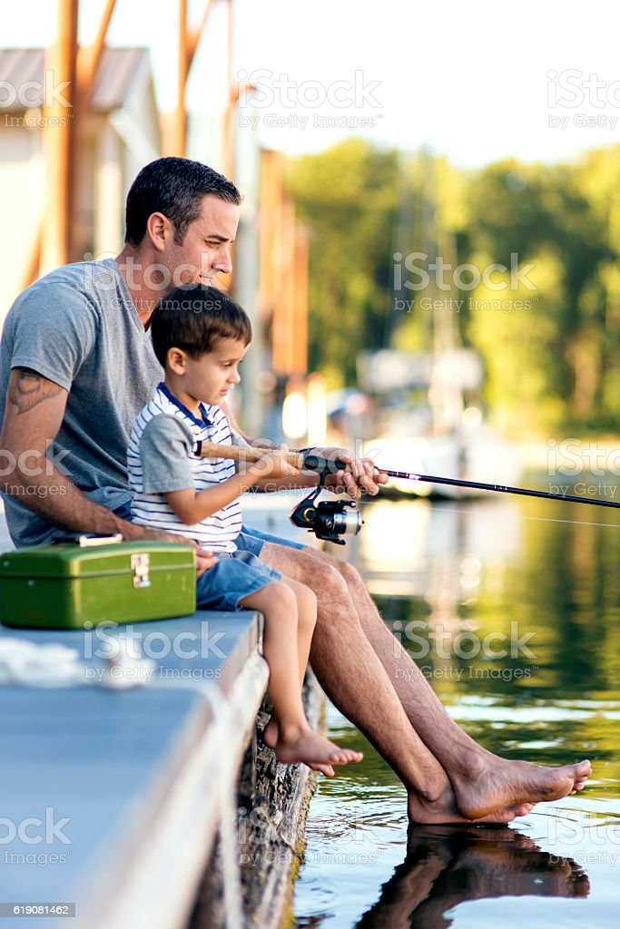Father teaching his son how to hold a fishing rod stock photo