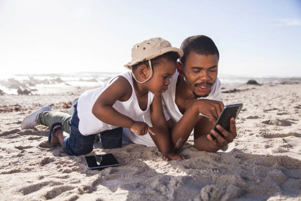 Father teaching his son how to use a cellphone on the beach. stock photo
