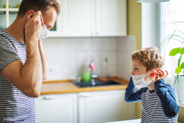 Father teaching his son how to wear protection mask against coronavirus stock photo