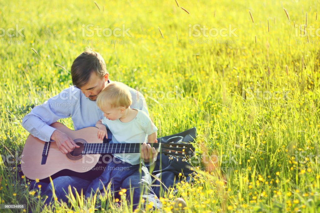 Father Teaching His Son To Play Guitar Outdoor Time Together