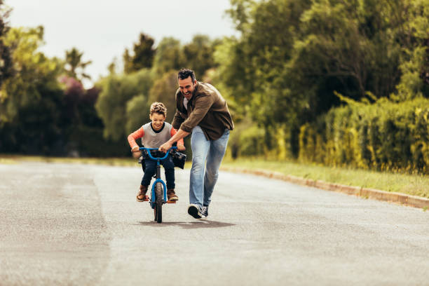 Father teaching his son to ride a bicycle Kid riding a bicycle while his father runs along holding the bicycle. Happy kid having fun learning to riding a bicycle with his father. jacoblund stock pictures, royalty-free photos & images