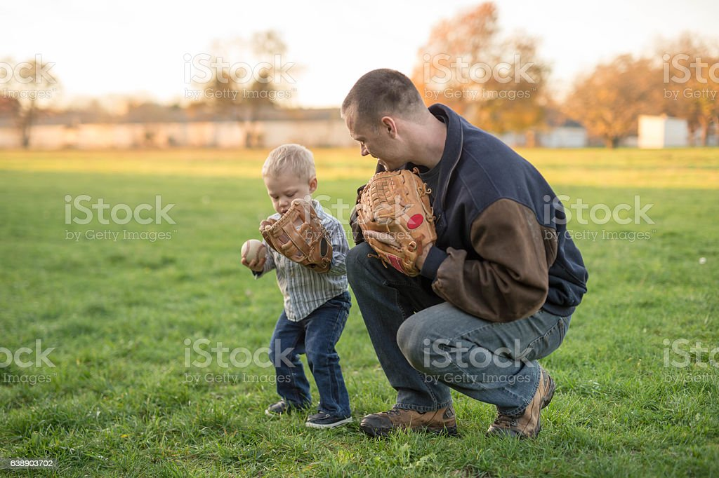 Father teaching his toddler son baseball in a park stock photo