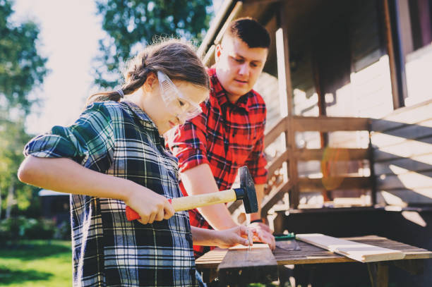 father teaching kid daughter to work with wood outdoor. Dad explaining how to use hammer and build wooden details. Country house on background stock photo