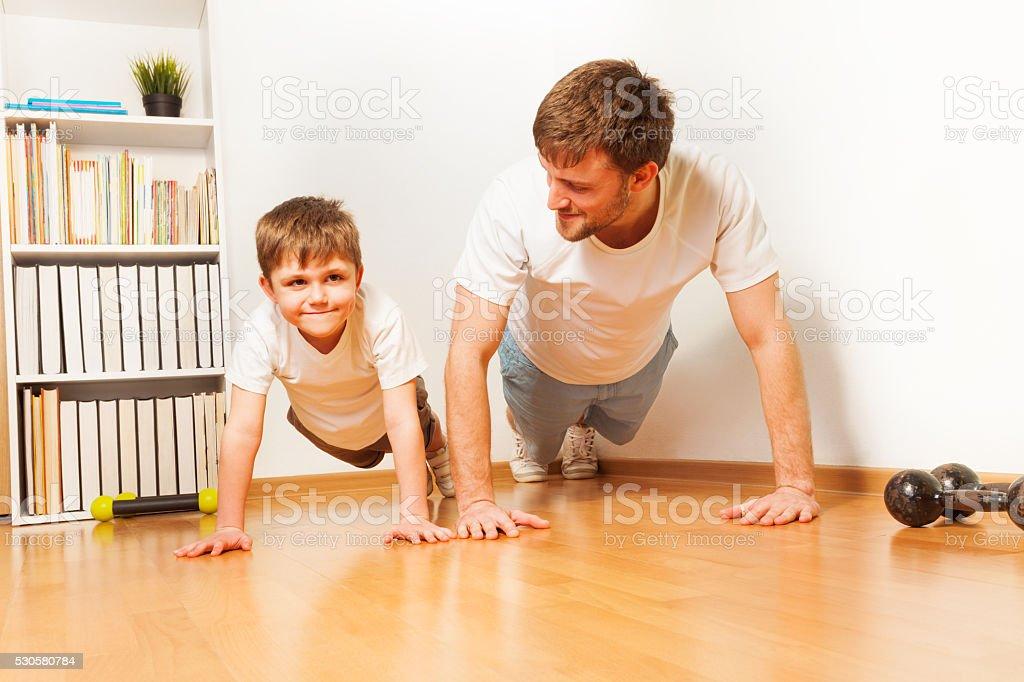 Father teaching kid son doing push-ups exercises stock photo