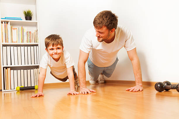 Father teaching kid son doing push-ups exercises stock photo