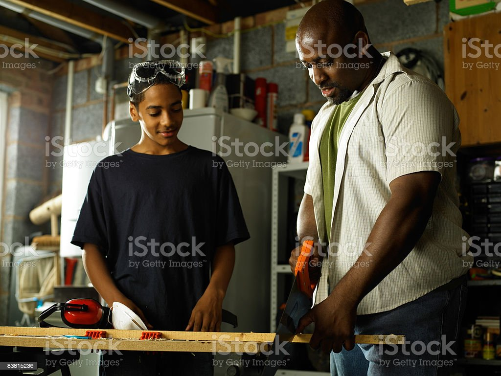Father teaching Son carpentry skills royalty-free stock photo