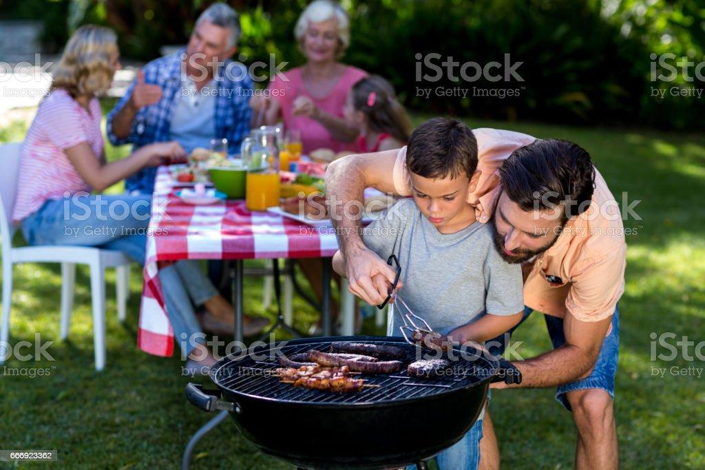 Père fils d'enseignement cuisson sur barbecue avec la famille - Photo