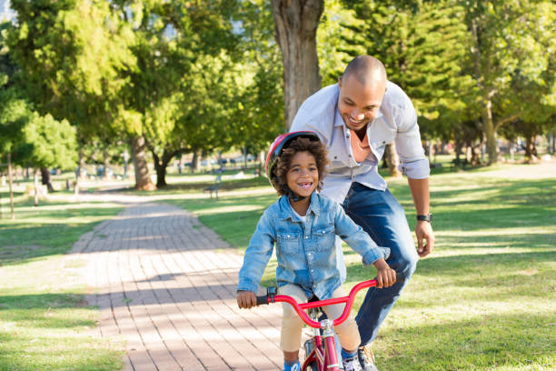 father teaching son cycling - cycling stock photos and pictures