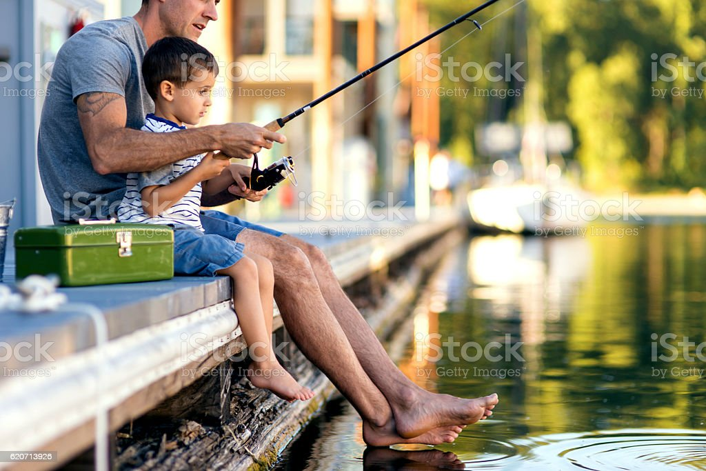 Father teaching son how to fish stock photo