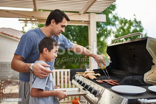 istock father teaching son how to grill hot dogs and bonding 1140662035