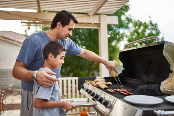 father teaching son how to grill hot dogs and bonding - жареный на гриле стоковые фото и изображения