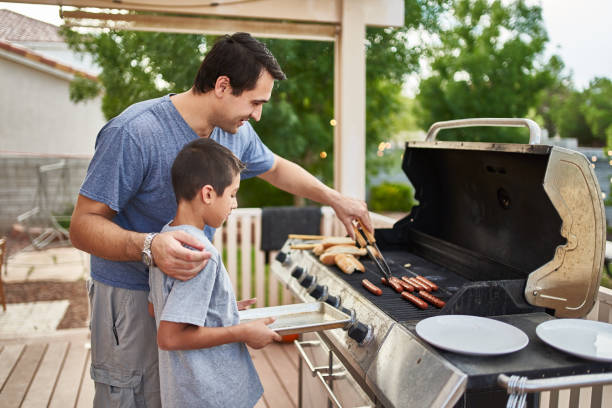father teaching son how to grill hot dogs and bonding stock photo