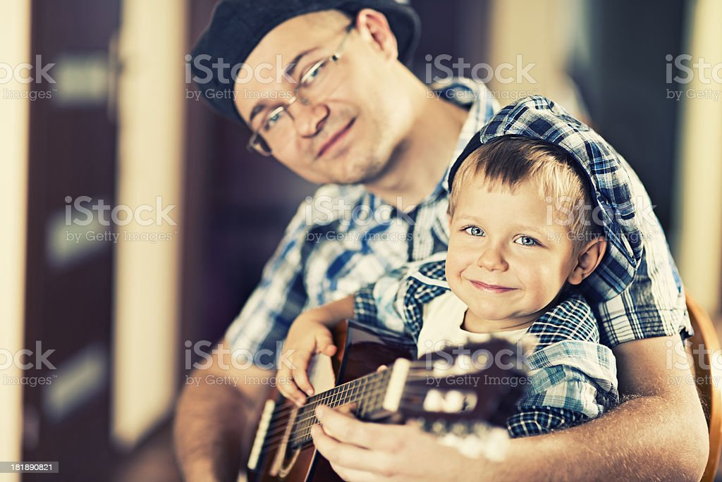 Father teaching son how to play a guitar royalty-free stock photo