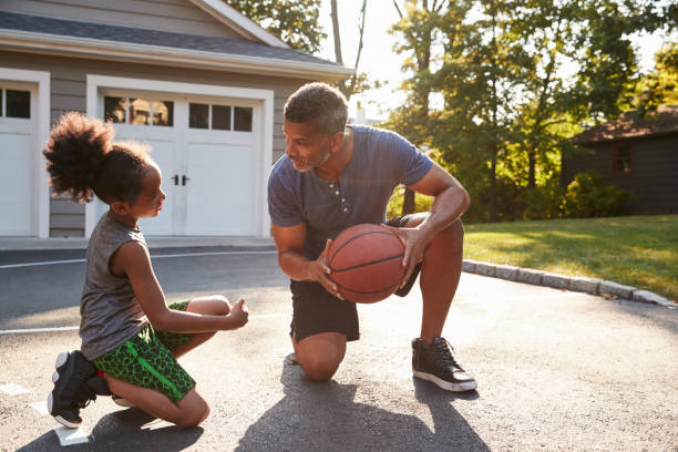 Father Teaching Son How To Play Basketball On Driveway At Home stock photo