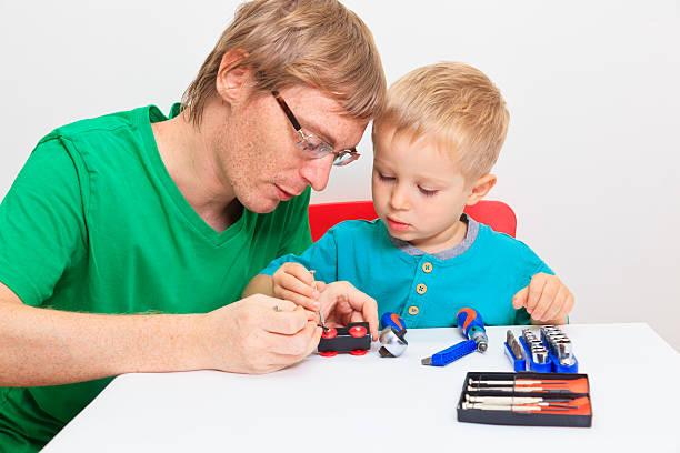 vater lehre sohn wie man reparatur spielzeug-eisenbahn - kindergarten handwerk stock-fotos und bilder
