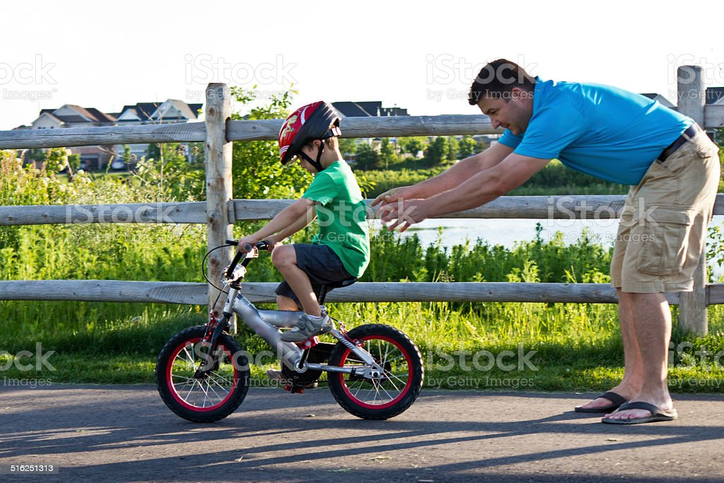 Father teaching son how to ride a bicycle stock photo