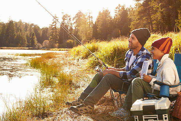 Father Teaching Son To Fish By Lake stock photo