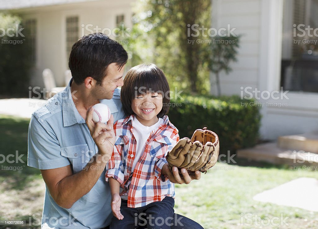 Father teaching son to play baseball stock photo