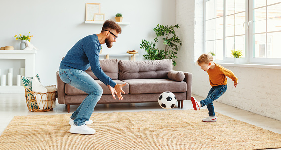 Bearded man in glasses  catching ball while teaching boy to play football in cozy room at home