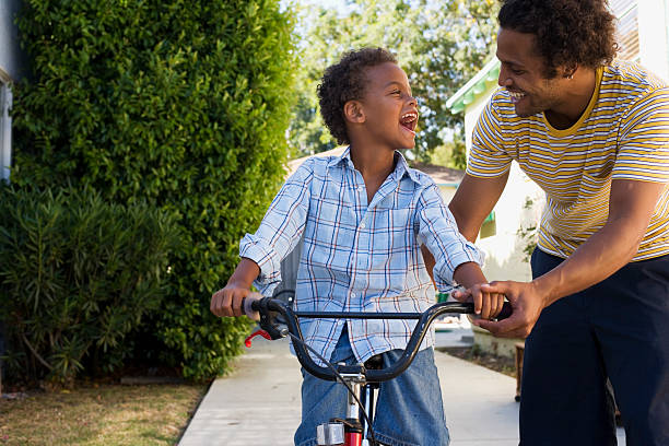 father teaching son to ride bicycle in driveway - riding stock photos and pictures