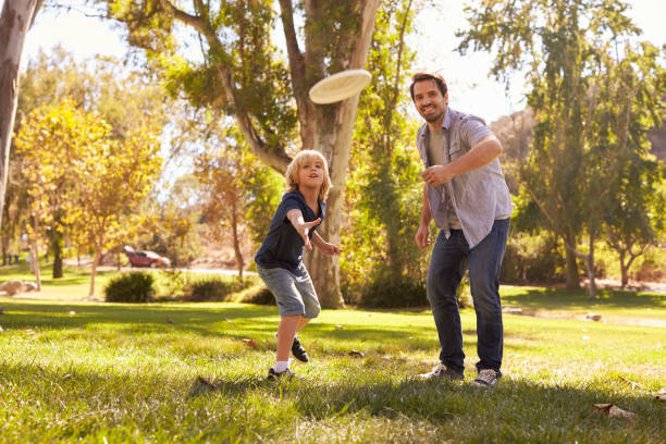 Father Teaching Son To Throw Frisbee In Park Father Teaching Son To Throw Frisbee In Park plastic disc stock pictures, royalty-free photos & images
