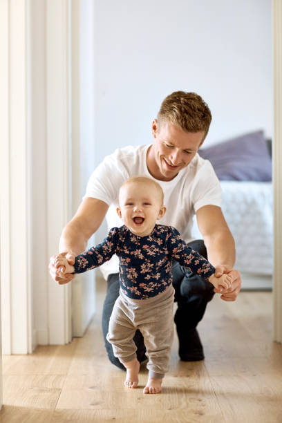 father teaching son to walk in corridor at home - first step stock photos and pictures