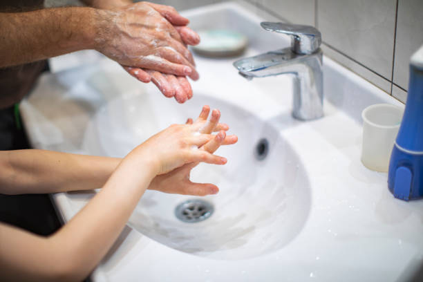 Father teaching son to wash hands stock photo