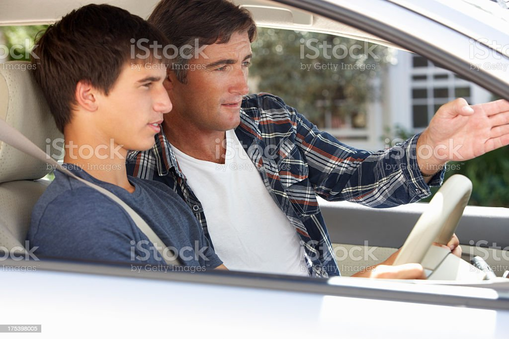 Father Teaching Teenage Son To Drive stock photo