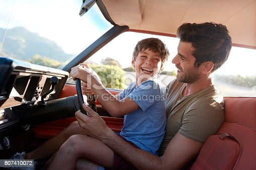 istock Father Teaching Young Son To Drive Car On Road Trip 807410072