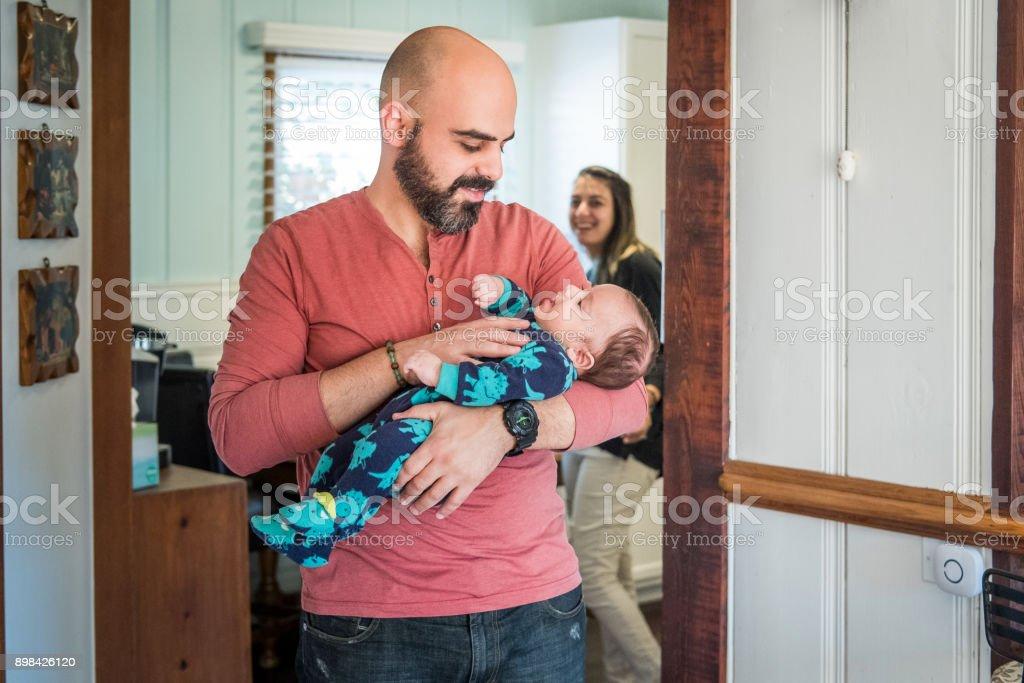 Father tends to infant son stock photo