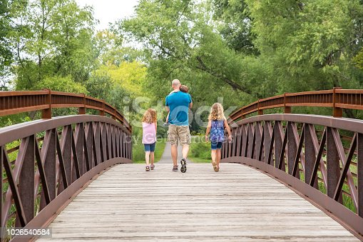 Rear view of a father and three children walking across a wooden and steel bridge in the woods on a late summer day. The father is carrying his toddler son in his arms while his daughters walk on both sides of him.