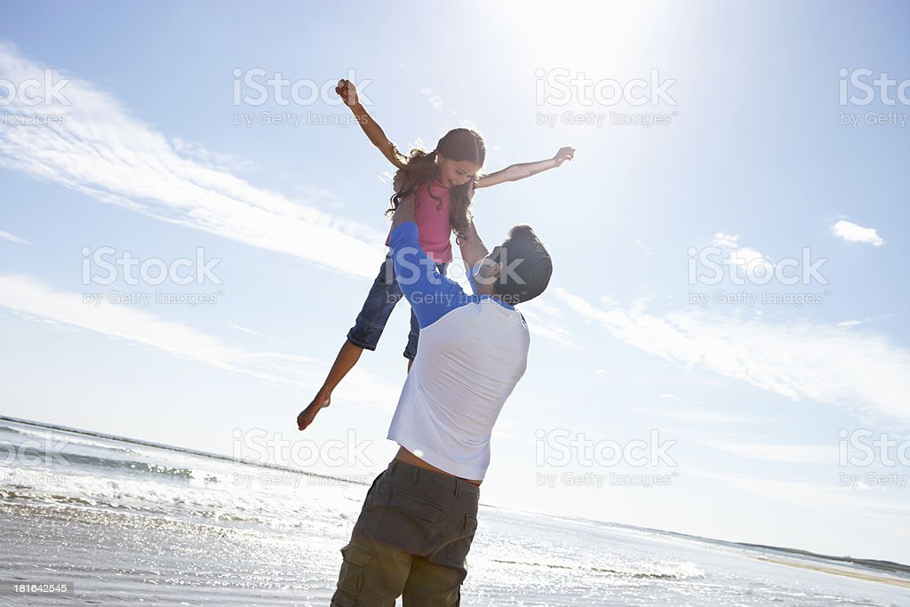 Father throwing daughter into air beside ocean stock photo