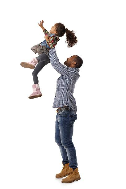 Father throwing little daughter in the air stock photo