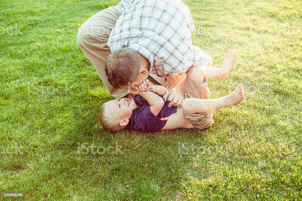 Father tickling his little barefoot boy making him laugh stock photo